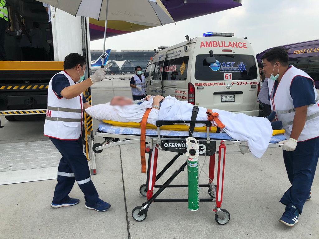 Patient on stretcher being transferred to a plane